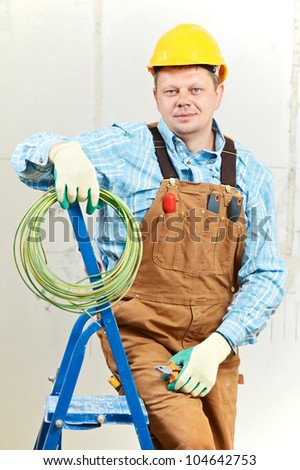 electrician worker with wiring cable and electric equipment tools - stock photo