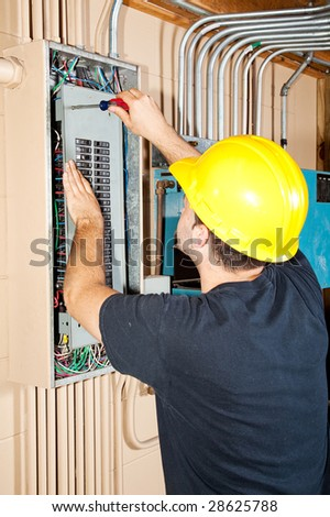 Electrician working on a breaker panel in a control room filled with exposed pipe. - stock photo
