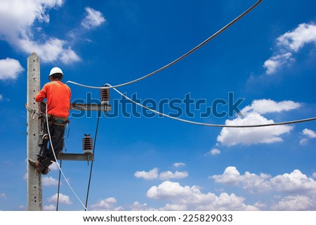 electrician working on electric power pole against blue sky  - stock photo