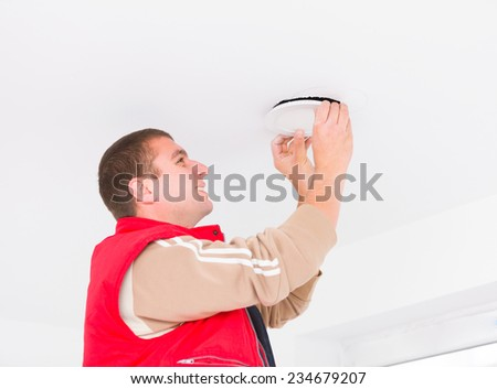 Electrician working with hanging cords on the wall, mounting light. - stock photo