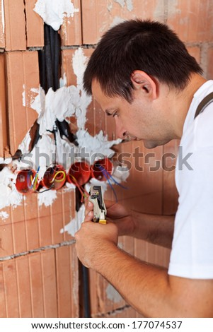 Electrician working with wires in a new building - removing insulation from the endings - stock photo
