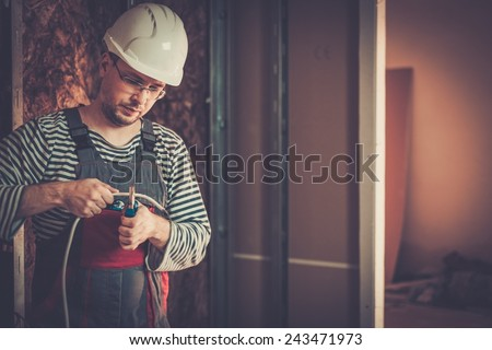 Electrician working with wires in new apartment  - stock photo