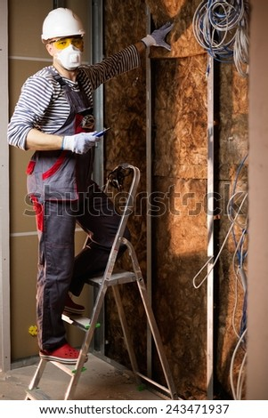 Electrician working with wires in new apartment on a ladder  - stock photo
