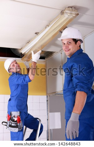 Electricians installing neon lights in the ceiling - stock photo