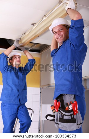Electricians installing neon on ceiling - stock photo