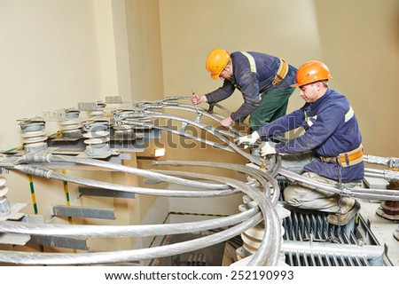 Electricians lineman repairman worker or installers at huge power industrial transformer installation work - stock photo