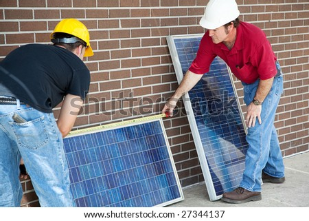 Electricians measuring solar panels they are about to install. - stock photo