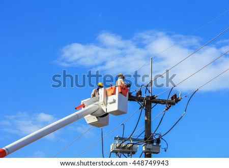 Electricians repairing wire of electric power system  - stock photo