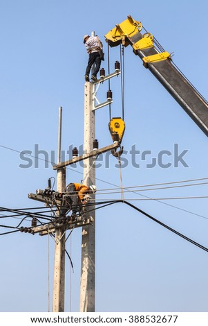 electricians repairing wire of the power line on electric power pole with crane  - stock photo