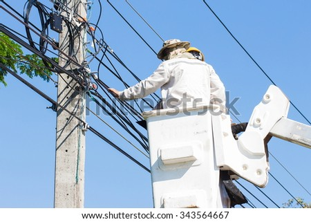 electricians repairing wire on electric power pole - stock photo