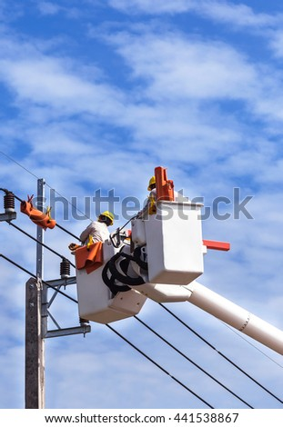 Electricians working on basket hydraulic lifting platform vehicle for repair wire of the power line   - stock photo