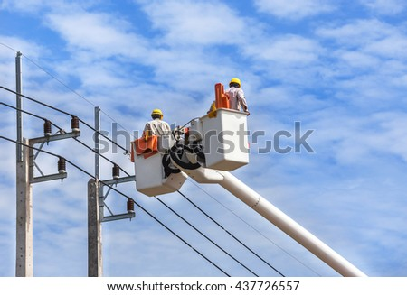 electricians working on hydraulic platform for repair wire of the power line. - stock photo