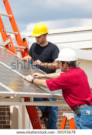 Electricians working to install solar panels on the side of a building. - stock photo