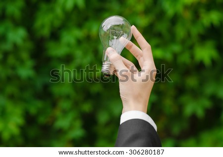 Electricity and business theme: a man in a black suit holding a light bulb against a background of green grass - stock photo