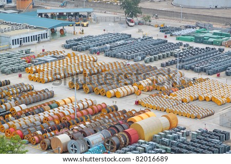 electricity cable on wooden spools and many transformer on the floor - stock photo