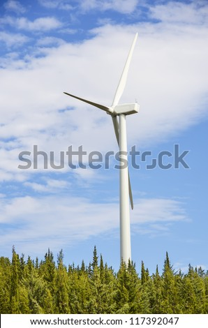 Electricity generating windmills on forest and sky with clouds - stock photo