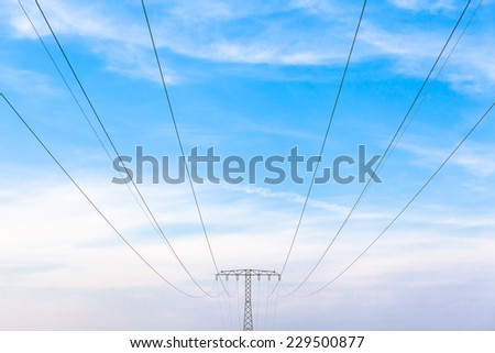 Electricity power cables and metal pylon construction in front of cloudy blue sky/Energy Powerline  - stock photo