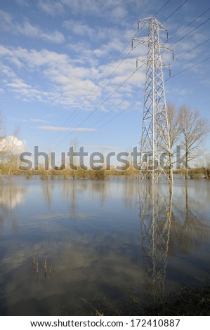 Electricity Power Lines cross Ashleworth Ham in flood, Viewed from banks of River Severn - stock photo