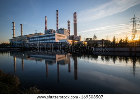 Electricity power plant near a river - stock photo