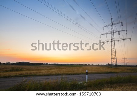 Electricity pylon against sunset blue hour with street - stock photo
