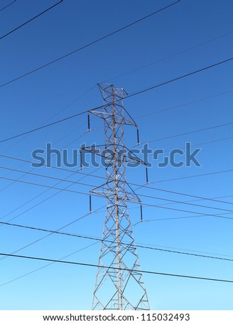 Electricity pylon and high tension metal structure transporting hydro power on insulated cables and wires for a traditional energy grid with electric lines criss crossing  a pattern on a blue sky. - stock photo