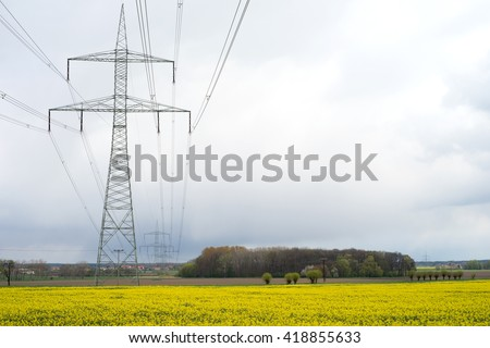 Electricity pylon and yellow rape field / Electricity pylon - stock photo