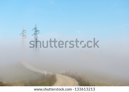 Electricity pylon in heavy fog at sunset - stock photo