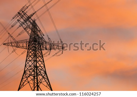 electricity pylon silhouetted against the sunset - stock photo