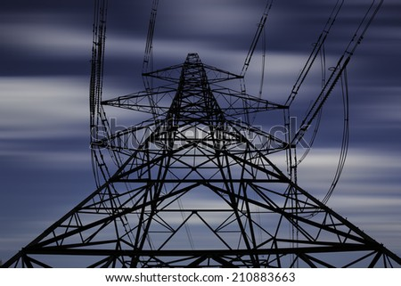 Electricity pylon with long exposure sky - stock photo