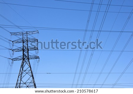 electricity pylon with power cable network against blue sky - stock photo