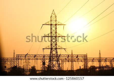 Electricity pylons and lines at sunset in India - stock photo