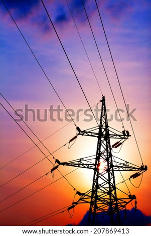 Electricity pylons and lines with dramatic sunset. - stock photo