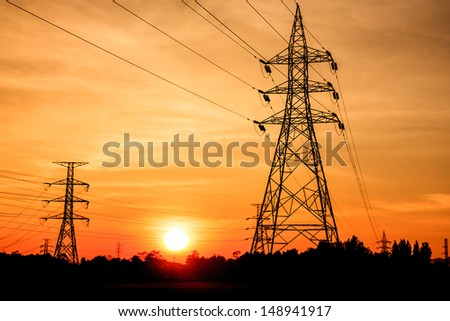 Electricity pylons at sunset - stock photo