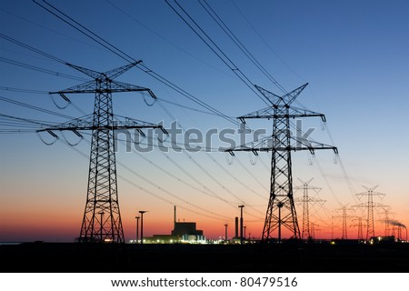 Electricity pylons at sunset with nuclear power plant at the horizon - stock photo