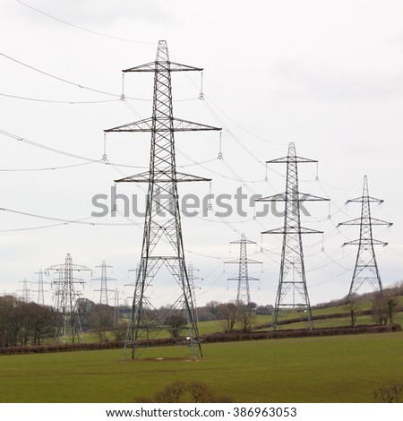 Electricity pylons bearing the power supply across a rural landscape UK - stock photo