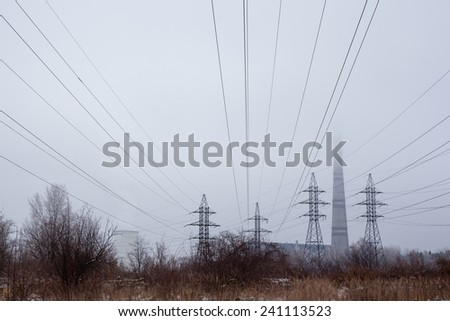Electricity pylons, power lines, smoke stack and cooling tower of the industrial plant in the foggy winter day. - stock photo
