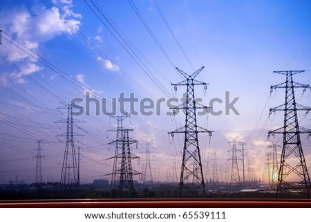 electricity pylons silhouetted against the sunset - stock photo