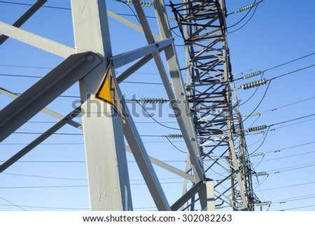 Electricity pylons with warning high voltage sign - stock photo
