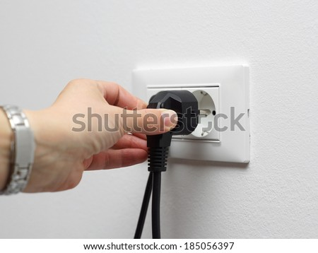 electricity savings concept, woman unplugged plug from the socket - stock photo