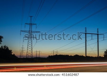 Electricity transmission power lines at sunset High voltage tower - stock photo