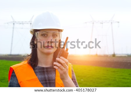 Electrification engineer talk a walkie-talkie ; Supervising female engineer for electrification using walkie- talkies near the transmission line - stock photo