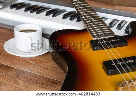 Electro guitar, piano and cap of coffee. Break during rehearsal - stock photo