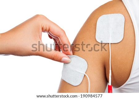 electrodes of tens device on shoulder, tens therapy, nerve stimulation - stock photo