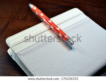 Electronic  book with pen wiht hearts on a wooden table - stock photo
