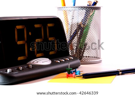 Electronic clock at office and office subjects: pen, pencils, a scratch paper. - stock photo