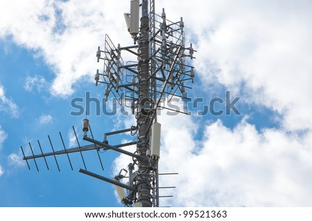 Electronic communications and cell phone tower under partially cloudy sky. Horizontal format - stock photo