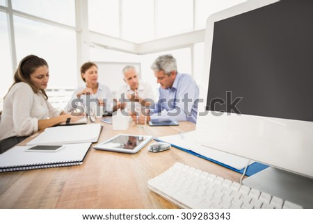 Electronic devices in front of talking business people in the office - stock photo