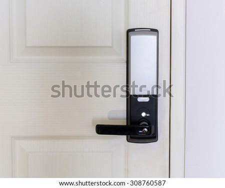 Electronic door lock on white wooden door - stock photo