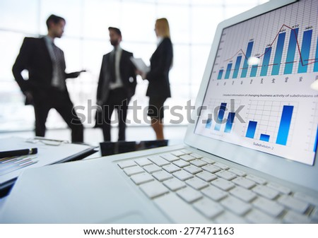 Electronic financial document in laptop on background of business partners interacting - stock photo