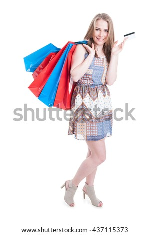 Electronic payment concept with pretty young female at shopping holding paper bags and credit card isolated on white background - stock photo